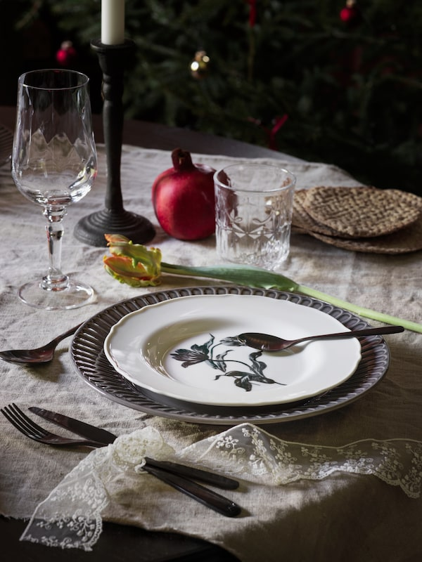 A traditional-looking table setting, with a white UPPLAGA plate at the centre layered on top of a blue plate.