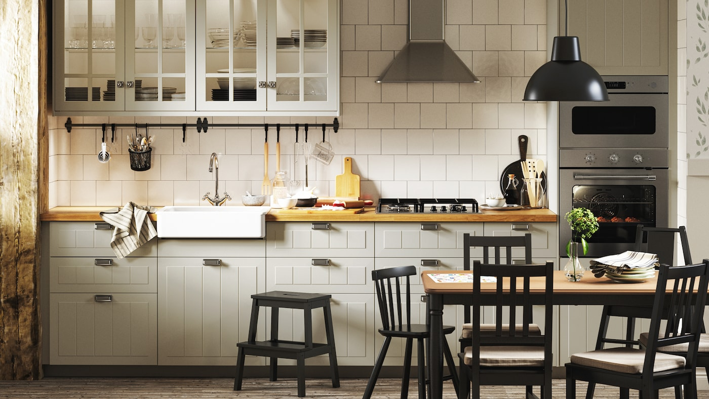 A traditional-style kitchen with beige cabinets, white tiles, wooden floors, floral wallpaper and a dark dining set.