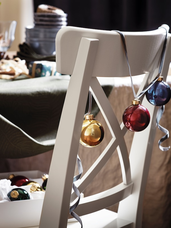 A traditional white wooden chair sitting at a dining table is decorated with a string of bright-coloured baubles.