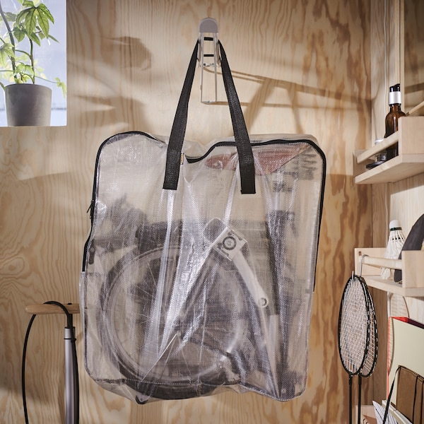 A transparent DIMPA storage bag with a foldable bicycle inside is hanging on a hook that's mounted on a wooden wall.
