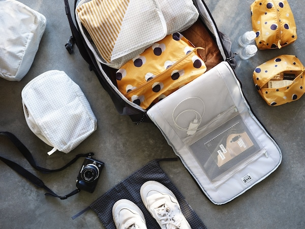 A travel bag organized with small bags inside.