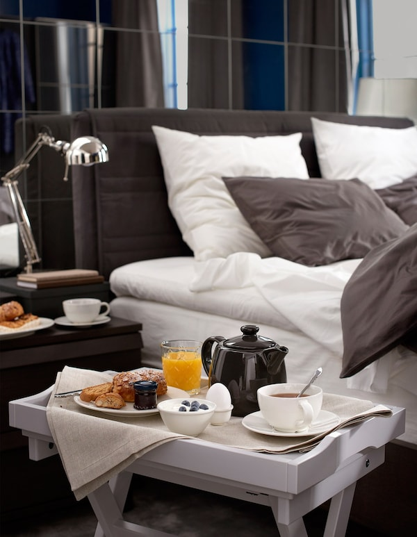 A tray table set with breakfast sits beside a large, cosy bed.