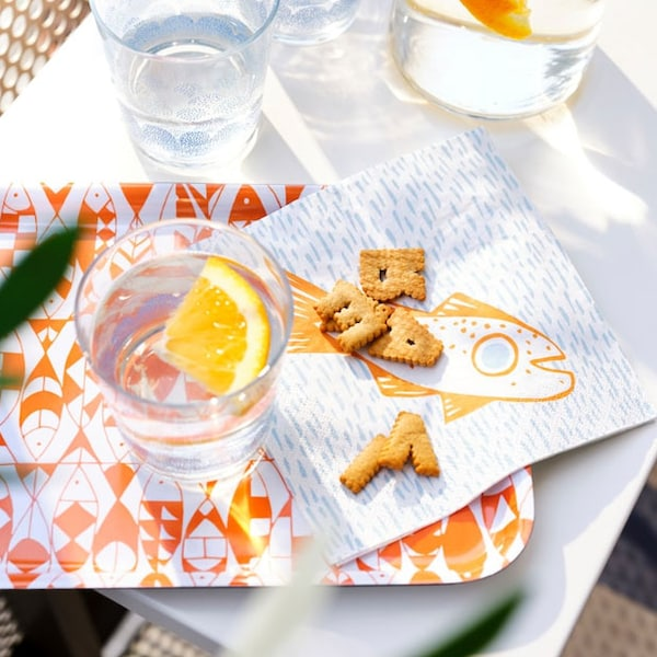 A tray with an orange/white pattern, painted glasses, a light blue/orange paper napkin, all from the SOMMARDRÖM collection.