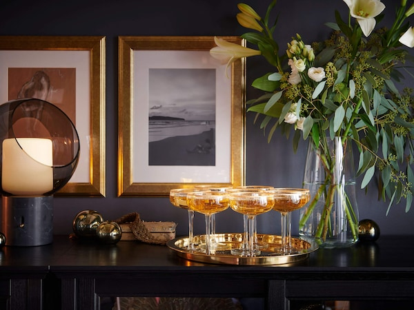 A tray with several champagne glasses on a surface with a vase of flowers.