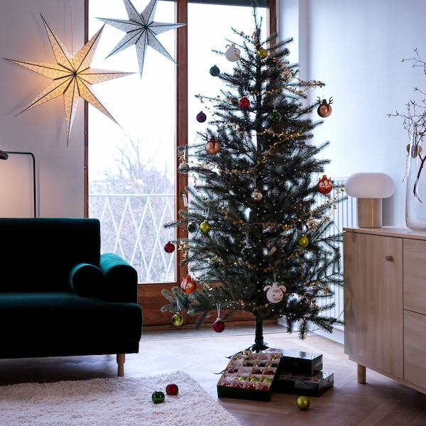 A tree is decorated with ornaments in a living room setting; an open box of baubles and other boxes are under the tree.