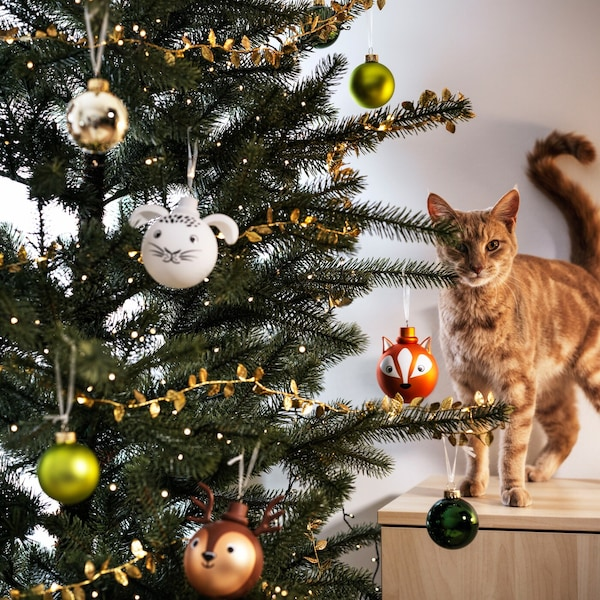 A tree is decorated with ornaments in a living room setting