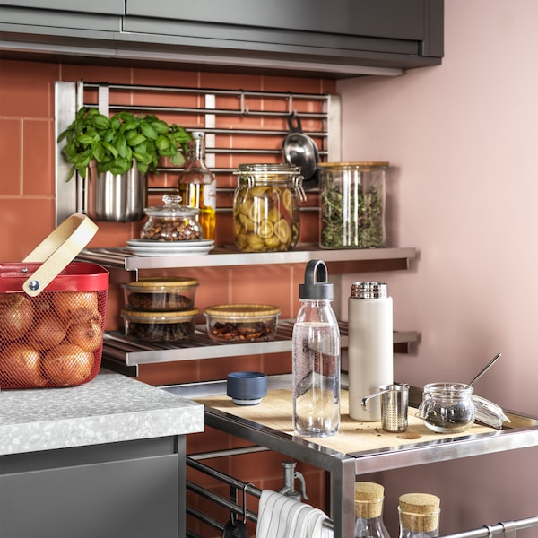 A trolley and a suspension rail with a wall grid/shelves in stainless steel, food in glass jars and onions in a red basket.