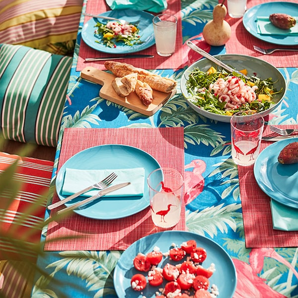 A tropical and summer themed tablescape with bright tableware and multiple summer food dishes.
