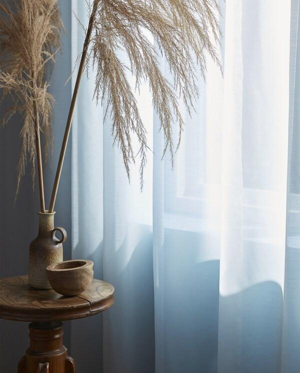 A türkiz színű HILJA függönyök és természetes anyagokból készült asztali dekorációk.