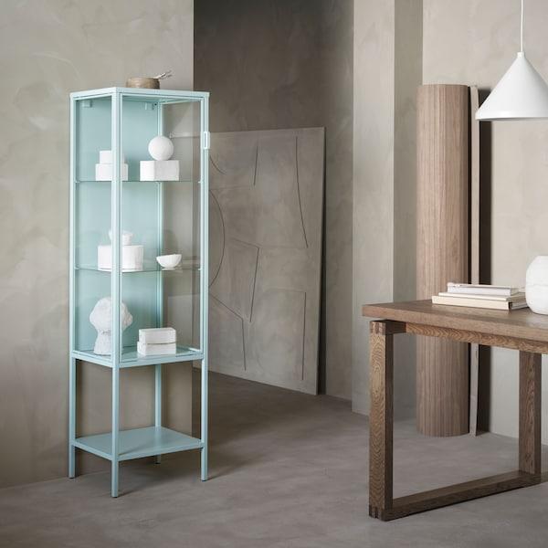 A türkizkék RUDSTA üvegajtós szekrény fehér díszekkel, minimalista, natúr enteriőrben.