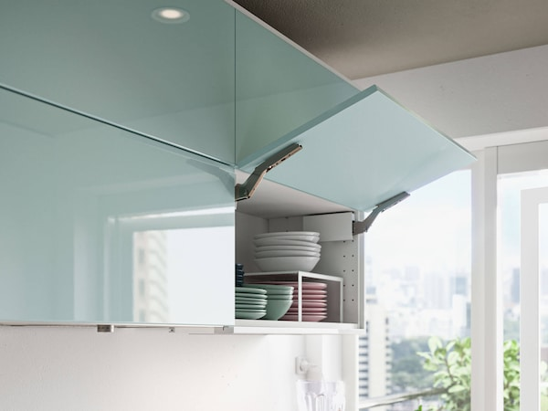 A turquoise blue set of cabinets with a window in the background.
