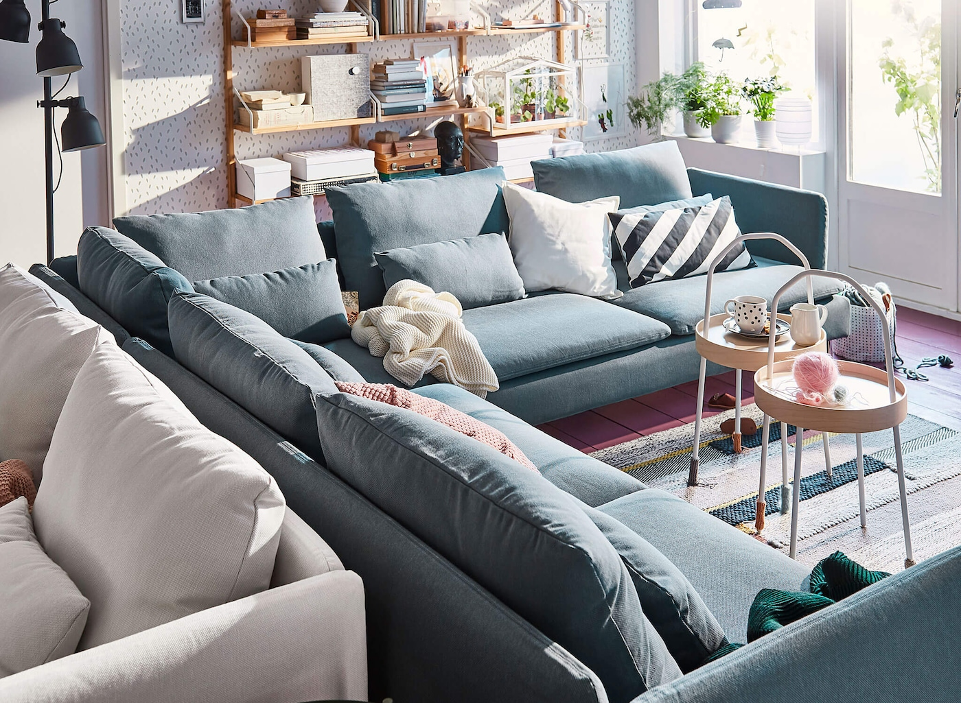 A turquoise corner sofa in a living room with white and black cushions and a throw blanket.