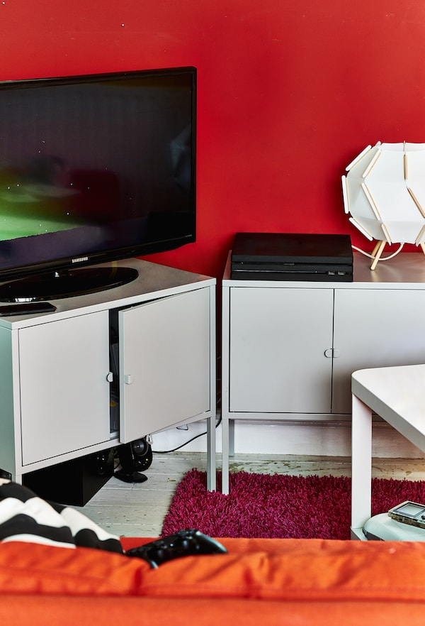 A TV and console on metal cabinets.