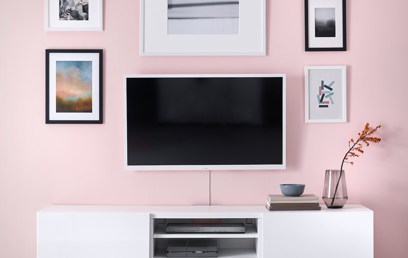 A TV mounted on a pink living room wall, beside pieces of wall art and above a white storage cabinet.