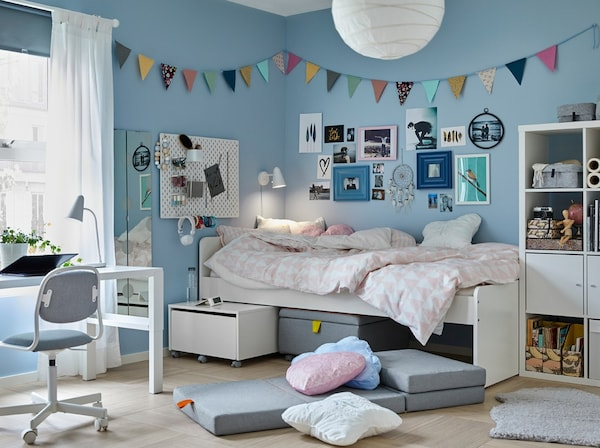 A tween bedroom with blue walls and white SLÄKT bed beside a white PÅHL desk and grey ÖRFJÄLL children's desk chair.