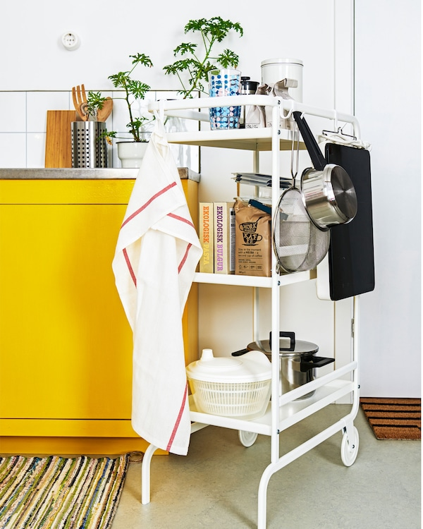 A two-wheeled trolley holding various kitchen accessories positioned right next to a kitchenette, as an extra surface.