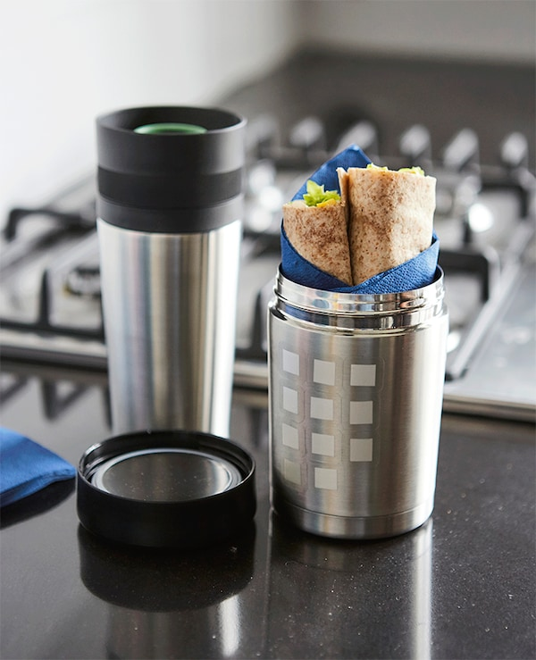 A vacuum flask thermos decorated with white stickers, filled with food, on a black worktop, near a cooker.