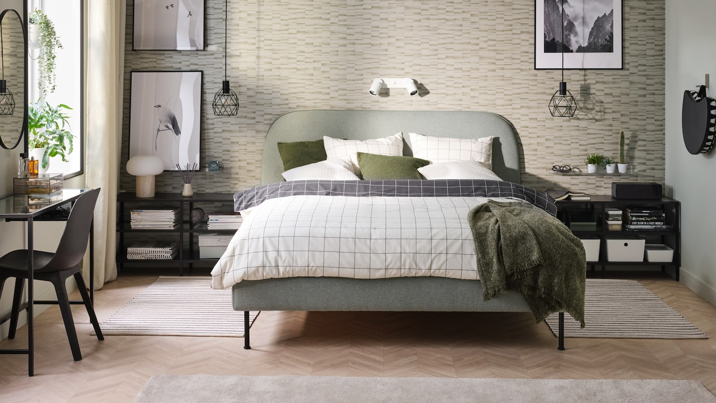 A VADHEIM upholstered bed with VITKLÖVER bed linen stands in a bedroom. VITTSJÖ TV benches stand at the sides of the bed.