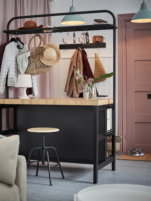 A VADHOLMA kitchen island with rack in black/oak used as room divider in a hallway and to store clothes and accessories.