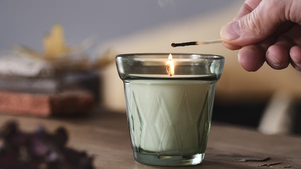 A VALDOFT candle in glass being lit with a match