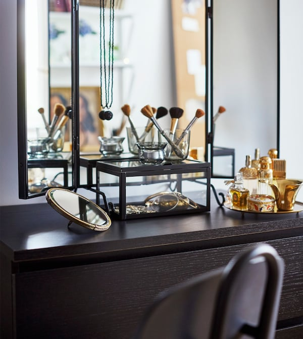 A vanity area with a wall mirror, black chair, black table top and make-up brushes on display.