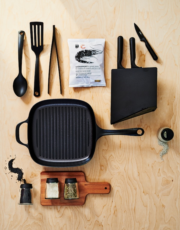 A VARDAGEN cast iron grill pan with tools, a knife block with knives, a wooden cutting board, spices, and frozen shrimp.
