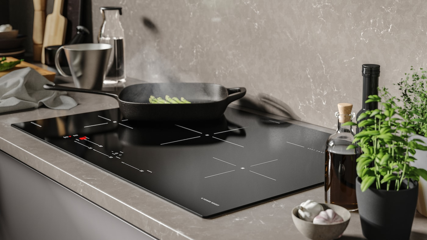 A VARDAGEN grill pan cooking broccoli on a black SÄRKLASSIG induction cooktop. There are kitchen utensils in the background.