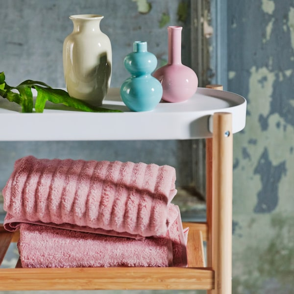 A variety of coloured vases placed on top of a white and wooden side table. Light pink towels are placed on the wooden rack.