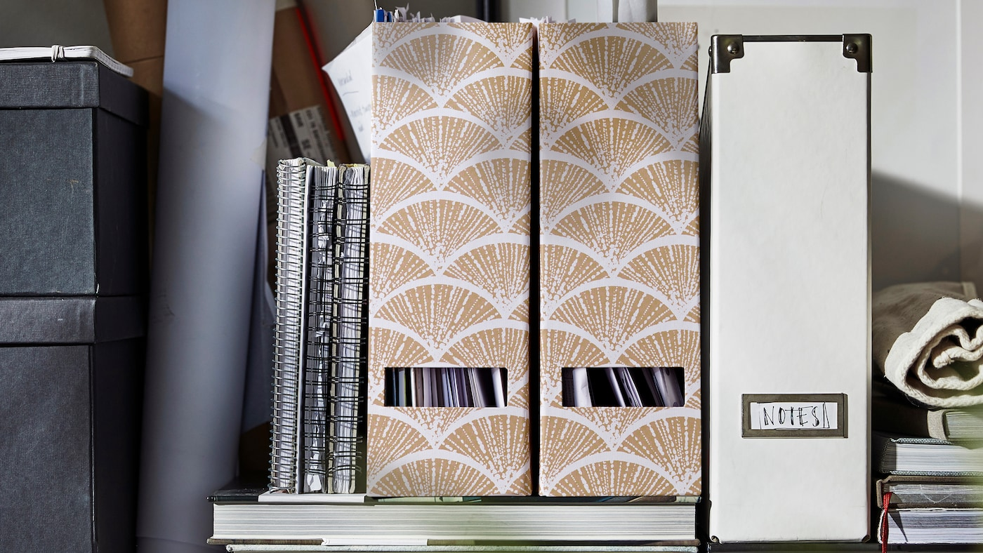 A variety of IKEA magazine files are placed on top of a couple of books. A few notebooks are leaning against them.