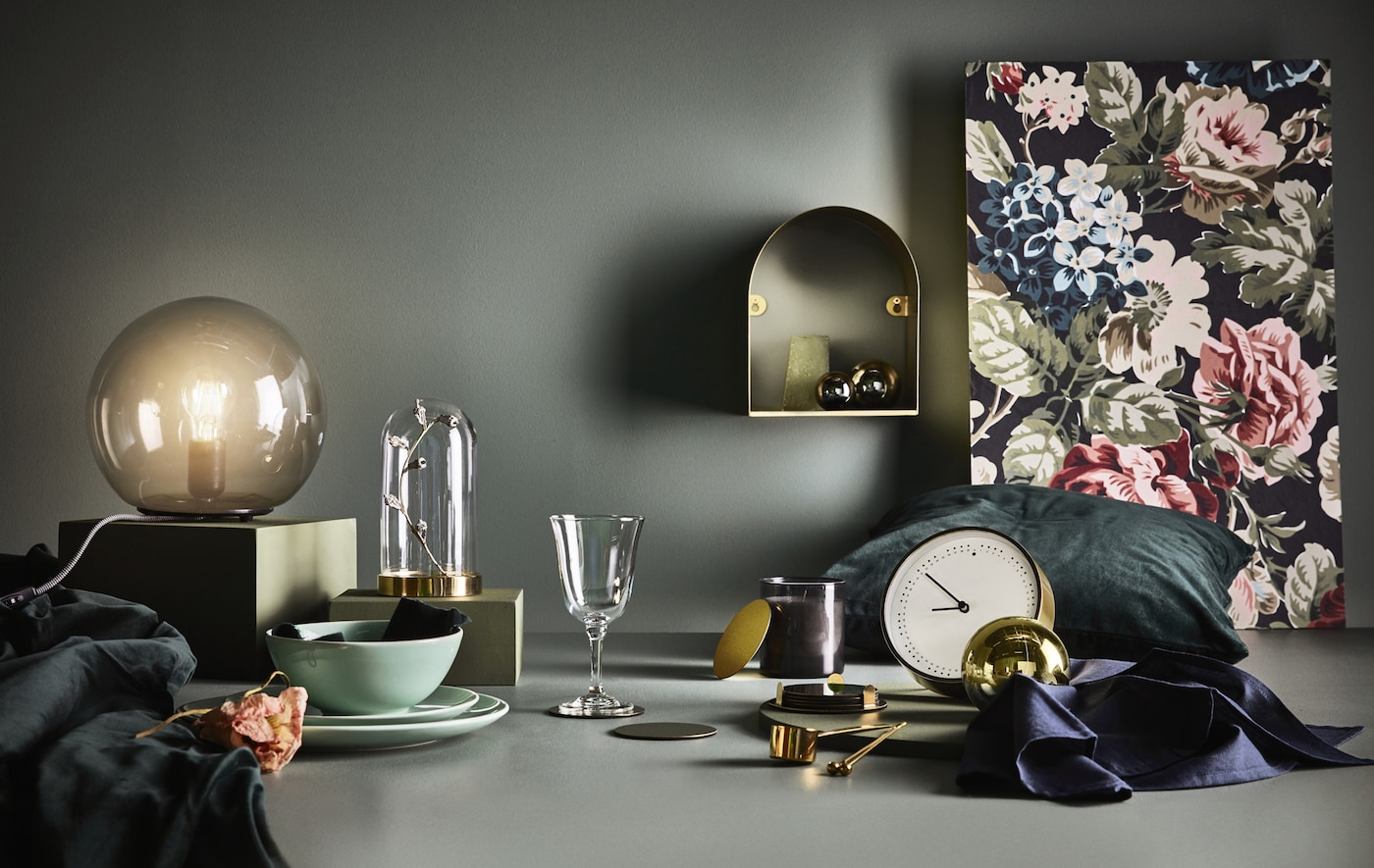 A variety of objects arranged on a surface against a dark backdrop, including a clock, table lamp and glass bell jar.