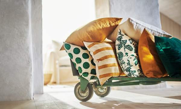 A variety of spring-coloured cushions sit on a wheeled trolley.