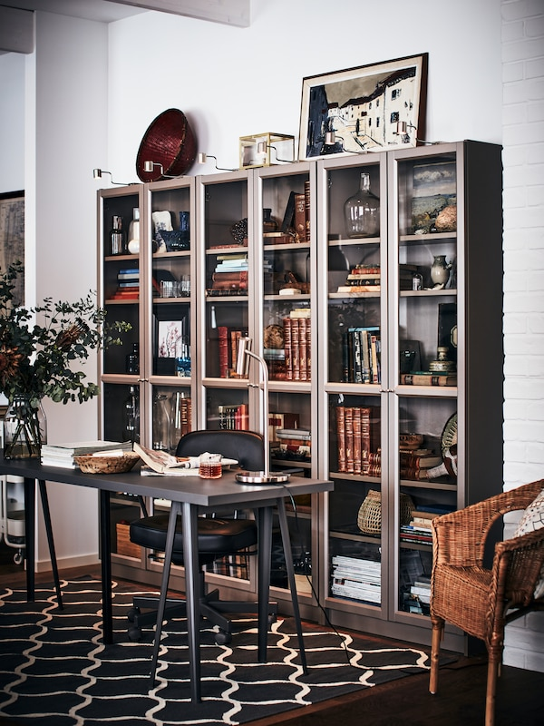 A vase of flowers and papers on a desk with NÄRSPEL trestles in front of three BILLY bookcases filled with books.