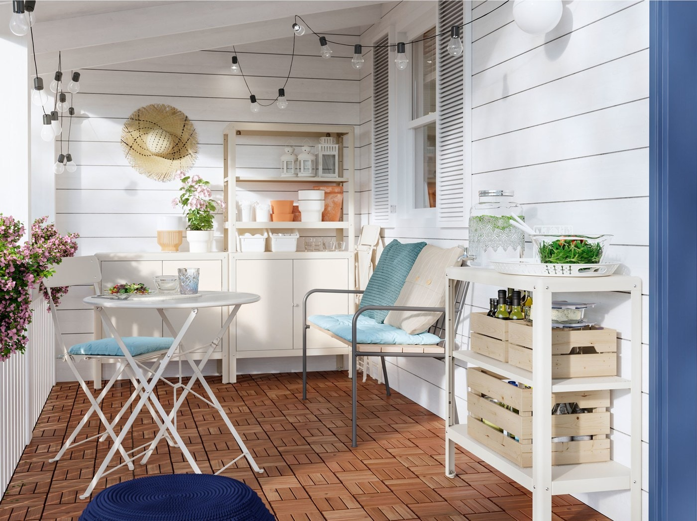 A veranda with a sofa, table and chair, with blue and cream cushions, an IKEA KOLBJÖRN off-white shelving unit and light chains.