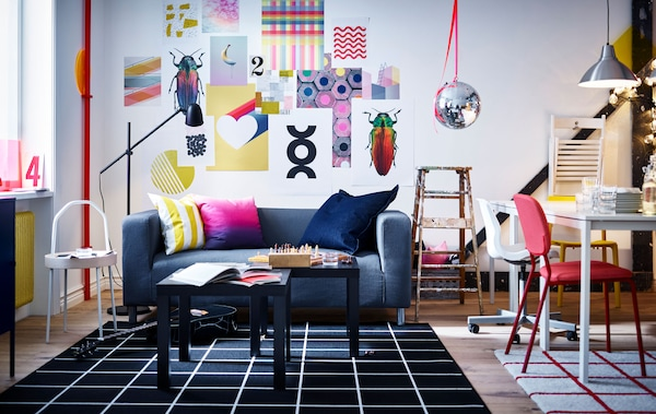 A vibrant living room and workspace with wall art, sofa, coffee tables, lamps, white tables, chairs, rugs and an old ladder.