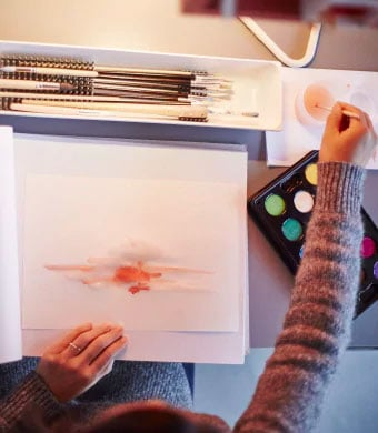A view from above of someone painting on some white paper on a grey desk