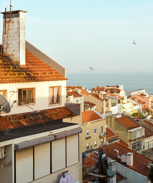 A view over red-tiled rooftops in a seaside town that leads to the water.