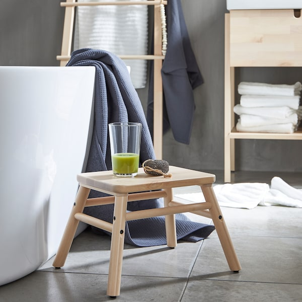 A VILTO step stool in birch wood placed beside a bathtub with a glass of green smoothie on it in a minimalistic bathroom.