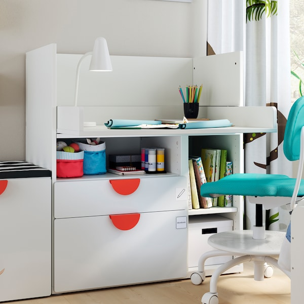 A VIMUND children's desk chair sits at a white SMÅSTAD desk with 2 drawers. There is a FUBBLA LED work lamp on the desk.