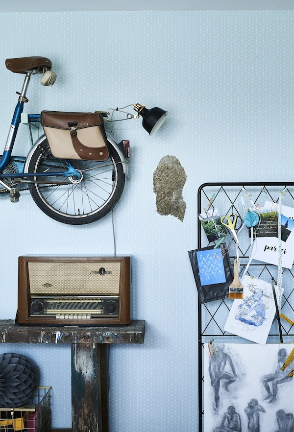 A vintage bike and trellis mounted on the wall with a vintage stereo below it, perched on a shelf.