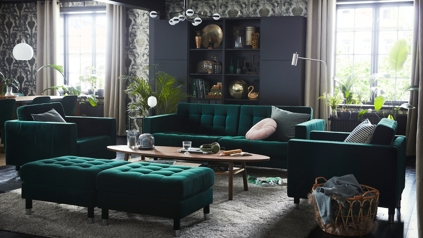 A vintage-style living room with a green velvet LANDSKRONA sofa, two armchairs and two footstools around a coffee table.