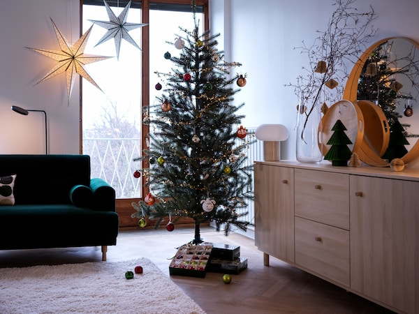 A VINTER 2021 holiday tree is decorated with ornaments in a living room setting; a box of baubles is under the tree.