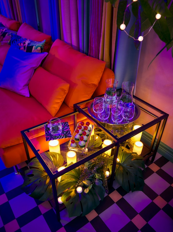 A VITTSJÖ nest of tables. Snacks on top, a carpet of FEJKA and SMYCKA artificial leaves and GODAFTON LED block candles below.
