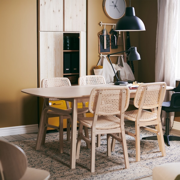 A VOXLÖV table with four chairs, standing on a MELHOLT flatwoven rug, a ROTBLÖTA wall clock on the wall and a hanging lamp.