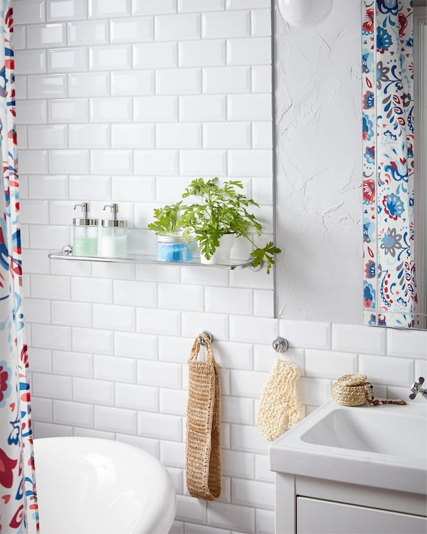 A VOXNAN glass shelf with chrome effect is placed close to the bathtub and wash basin and store soap and plants.