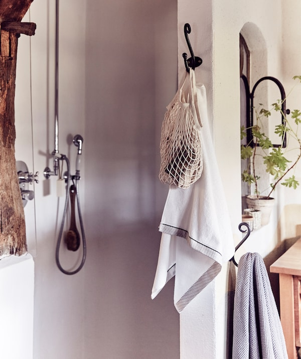 A walk-in shower area and towels hanging on hooks.