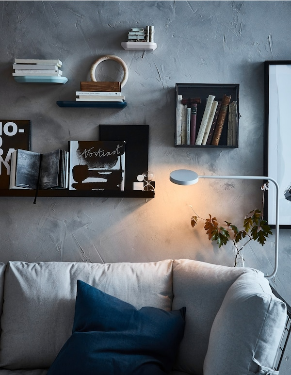 A wall behind a sofa decorated with display boxes and picture ledges loaded with books and pictures.