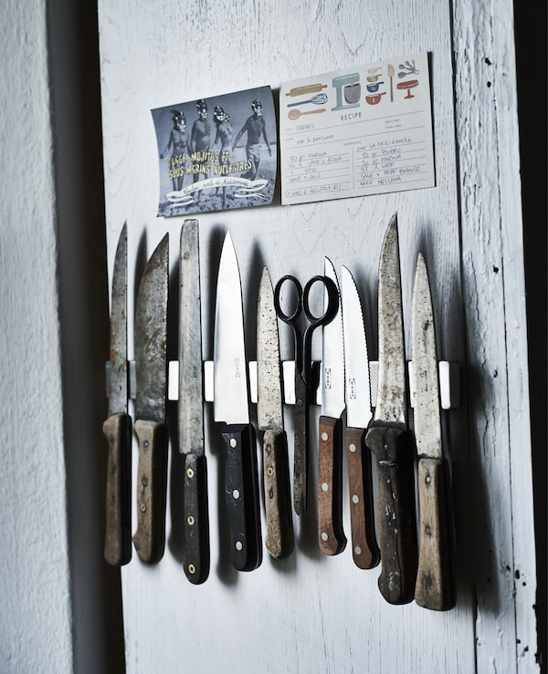 A wall display of a kitchen knife collection.