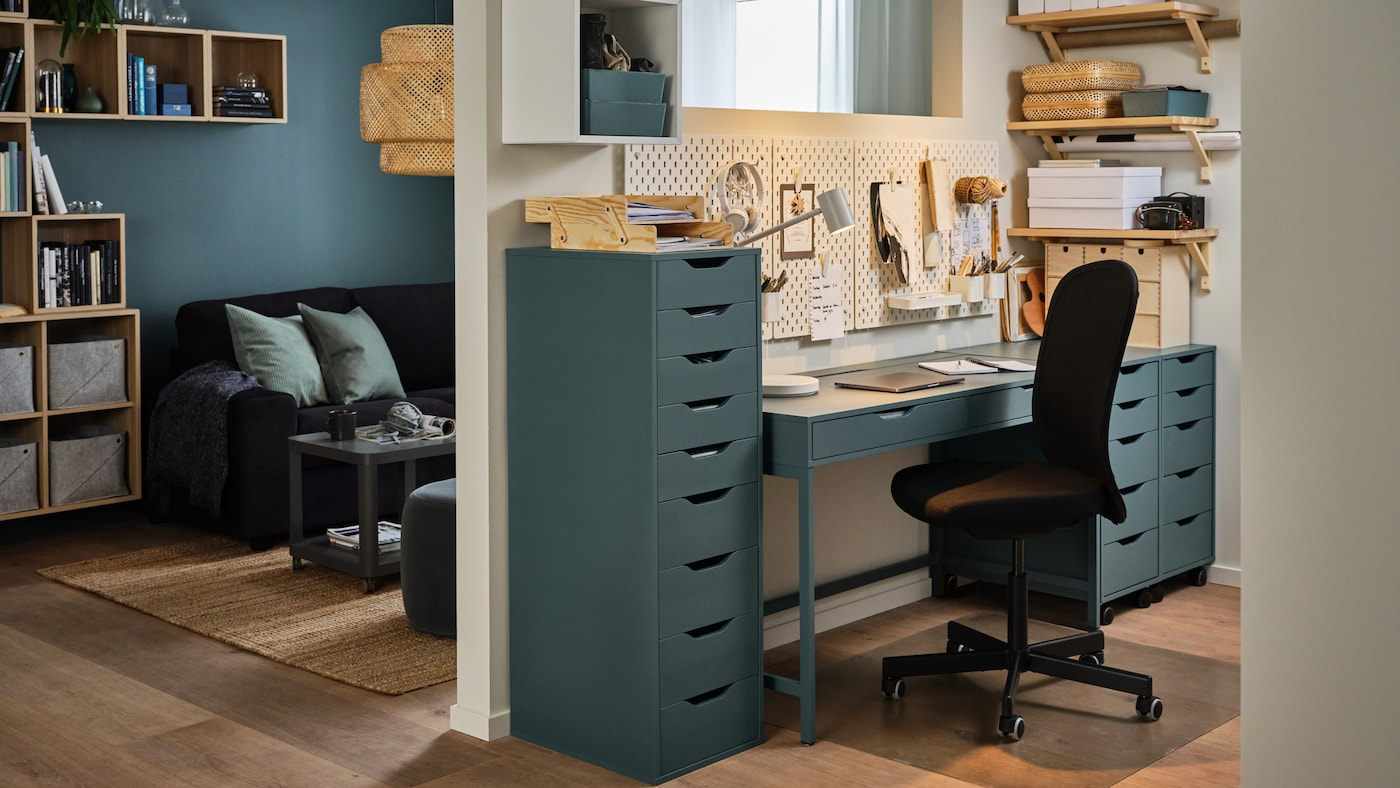 A wall dividing a living room and a workspace at home, gray-turquoise desk and drawer units, a black office chair.