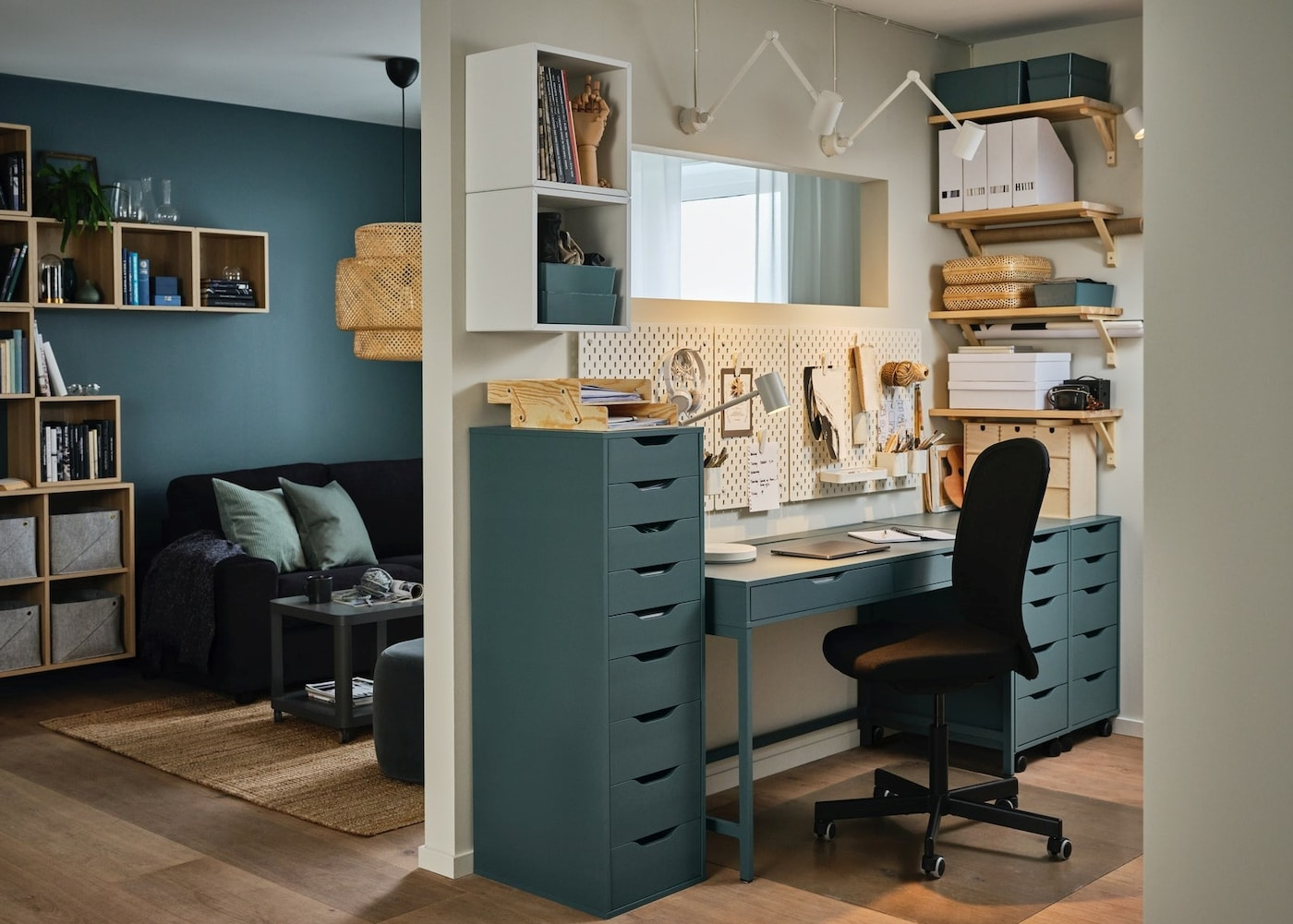 A wall dividing a living room and a workspace at home, grey-turquoise desk and drawer units, a black office chair.