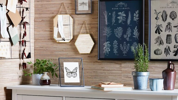 A wall in a dining room with a set of KNOPPÄNG frames with garden posters, LASSBYN mirrors and SÖSDALA memo boards.